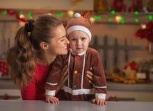 El retrato de la madre y del bebé en la Navidad adornó la cocina Fotografía de archivo