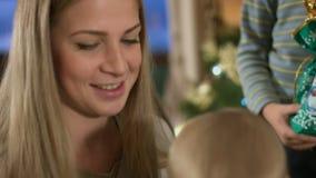 El retrato de la mamá con tres pequeños niños con los regalos acerca al árbol de navidad almacen de video