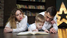 El retrato de la mamá joven de la familia, el hijo y el papá están leyendo un libro juntos almacen de video