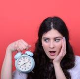 El retrato de la mirada de la muchacha asustó en el reloj contra fondo rojo Fotografía de archivo libre de regalías