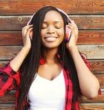 El retrato de la moda de la mujer africana joven sonriente feliz con el goce de los auriculares escucha la música Foto de archivo libre de regalías