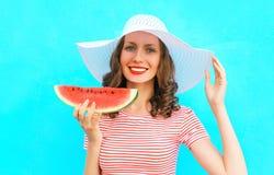 El retrato de la moda de la mujer sonriente feliz está llevando a cabo una rebanada de sandía en un sombrero de paja Fotografía de archivo