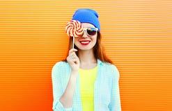 El retrato de la moda que es la mujer joven sonriente feliz se cierra el ojo con una piruleta en el palillo sobre naranja colorid Imagen de archivo