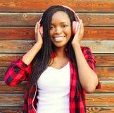 El retrato de la moda que la mujer africana sonriente feliz con los auriculares está gozando escucha la música Foto de archivo