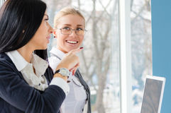 El retrato de la morenita hermosa de dos mujeres jovenes y los compañeros de trabajo rubios acercan a la ventana de la oficina en  Fotos de archivo libres de regalías