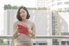 El retrato de la muchacha adolescente asiática lee soportes de libro rojos y se viste para arriba Foto de archivo