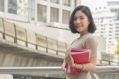 El retrato de la muchacha adolescente asiática lleva a cabo soportes de libro rojos y se viste para arriba Fotografía de archivo libre de regalías