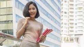 El retrato de la muchacha adolescente asiática lleva a cabo soportes de libro rojos y se viste para arriba Imagenes de archivo