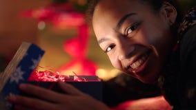 El retrato de la muchacha adolescente está abriendo el regalo y su cara es brillante con la luz almacen de video