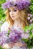 El retrato de la muchacha adolescente hermosa con la guirnalda de la lila florece Imagenes de archivo