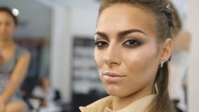 El retrato de la muchacha atractiva con maquillaje extremo mira la cámara los peluqueros almacen de video
