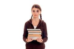 El retrato de la muchacha atractiva joven del estudiante en deporte marrón viste con muchos libros en las manos aisladas en blanc Imagen de archivo libre de regalías