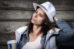 El retrato de la muchacha atractiva linda hermosa en chaqueta del sombrero y del dril de algodón lleva a cabo la bebida fresca en Fotografía de archivo