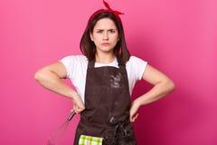 El retrato de la muchacha cabelluda oscura en el delantal manchado con la harina, la camiseta y la banda roja del pelo, soportes  imagenes de archivo