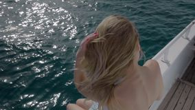 El retrato de la muchacha caucásica en bikini y las gafas de sol en la cubierta de un océano navegan en el mar Él juega con el pe almacen de video