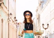 El retrato de la muchacha con el teléfono móvil y la ciudad trazan Fotos de archivo