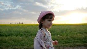 El retrato de la muchacha corriente, niño femenino sonriente, corre a lo largo del camino del campo, niño feliz que se divierte f almacen de video