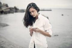 El retrato de la muchacha del adolescente que camina en la playa está comprobando en línea el teléfono móvil que espera un mensaj Imagen de archivo