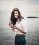 El retrato de la muchacha del adolescente que camina en la playa está comprobando en línea el teléfono móvil que espera un mensaj Foto de archivo libre de regalías