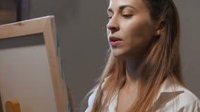 El retrato de la muchacha de The del artista se coloca en el caballete, pinta una imagen, ella está muy interesado 4K MES lento metrajes