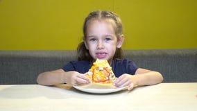 El retrato de la muchacha del pequeño niño come la rebanada de pizza en el café con las paredes amarillas almacen de video