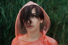 El retrato de la muchacha en impermeable rojo debajo de la lluvia Imágenes de archivo libres de regalías