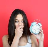 El retrato de la muchacha en la mirada del caos asustó en el reloj contra vagos rojos Foto de archivo