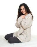 El retrato de la muchacha en vestido hogareño se sienta en el piso de la piel, fondo blanco Foto de archivo libre de regalías