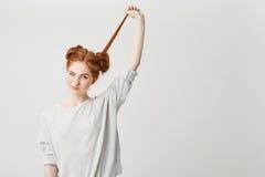 El retrato de la muchacha hermosa joven del pelirrojo desata el pelo conmovedor del bollo sobre el fondo blanco Foto de archivo