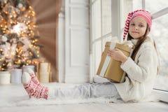 El retrato de la muchacha de mirada agradable adorable lleva la ropa caliente cómoda, caja de regalo envuelta controles, recibe e fotos de archivo libres de regalías