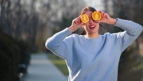 El retrato de la muchacha morena atractiva delgada con los labios rojos plantea en cámara con ayuda dos mitades de la naranja que almacen de metraje de vídeo