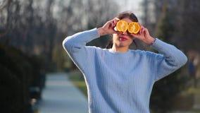 El retrato de la muchacha morena atractiva delgada con los labios rojos plantea en cámara con ayuda dos mitades de la naranja que metrajes