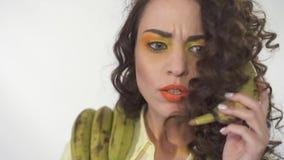 El retrato de la muchacha rizada joven con brillante compone la imitación de una conversación telefónica seria con un plátano Cám almacen de metraje de vídeo