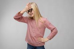 El retrato de la muchacha rubia adorable sonriente del adolescente del dulce atractivo en vidrios en blusa rosada en fondo gris o Foto de archivo libre de regalías