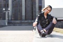 El retrato de la muchacha rubia de moda con los vidrios del ojo que llevan una roca ennegrece estilo al aire libre en la ciudad Foto de archivo