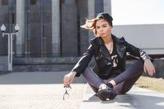 El retrato de la muchacha rubia impudente de moda con los vidrios del ojo que llevan una roca ennegrece estilo al aire libre en l Foto de archivo