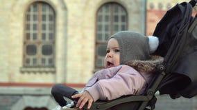 El retrato de la muchacha de un año se sienta en cochecito Ciérrese para arriba de bebé que viaja Tiempo fr?o 4K almacen de video