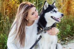 El retrato de la muchacha y del perro fornido está descansando cerca Imagen de archivo