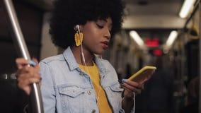El retrato de la mujer afroamericana joven con los auriculares que escucha la música, canta y baile divertido en transporte públi metrajes