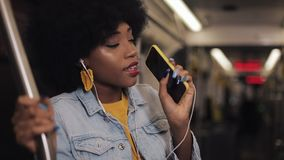 El retrato de la mujer afroamericana joven con los auriculares que escucha la música, canta y baile divertido en transporte públi almacen de video