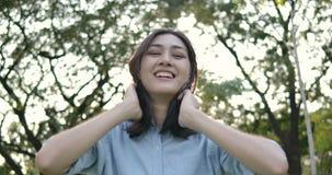 El retrato de la mujer asiática atractiva joven sonríe feliz en cámara en un parque del verano en la puesta del sol almacen de metraje de vídeo