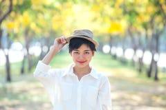 El retrato de la mujer asiática hermosa que se coloca en la floración florece Imagenes de archivo