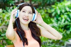 El retrato de la mujer asiática relaja estilo con la canción y el auricular imagen de archivo