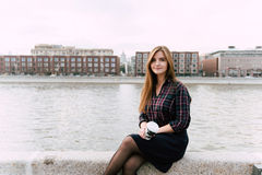 El retrato de la mujer bonita joven que se sienta con se lleva la taza de café en un embarcadero del río en día hermoso del otoño Imagenes de archivo