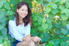 El retrato de la mujer bonita que se sienta en verde sale del arbusto y del smilin Foto de archivo