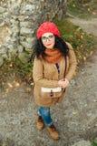 El retrato de la mujer caucásica joven en rojo hizo punto el sombrero al aire libre en parque Foto de archivo libre de regalías