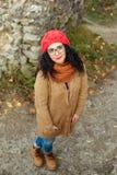 El retrato de la mujer caucásica joven en rojo hizo punto el sombrero al aire libre en parque Imágenes de archivo libres de regalías