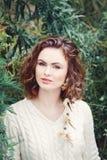 El retrato de la mujer caucásica blanca sonriente hermosa de la muchacha con los ojos pardos largos del pelo rizado, en el suéter Imagen de archivo