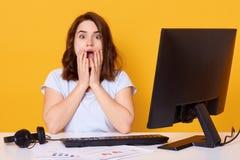 El retrato de la mujer chocada que se sienta en el escritorio blanco cerca del ordenador, mirando la cámara con la boca abierta y foto de archivo libre de regalías