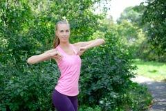 El retrato de la mujer deportiva que hace estirar ejercita en parque antes de entrenar Atleta de sexo femenino que se prepara par Imagenes de archivo